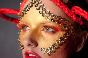 modelka w artystycznym złoto-czerwonym makijażu